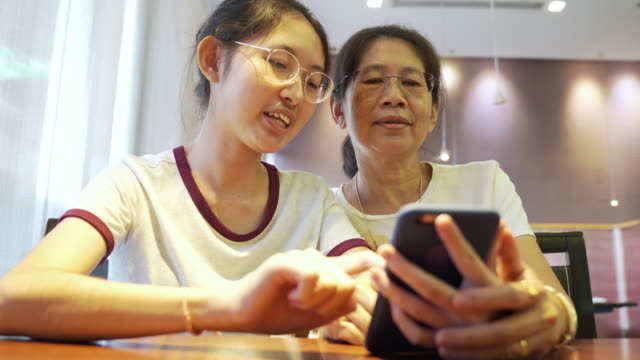 asian family young teenage and mother on vacation relaxing using digital tablet and smart phone for doing homework at home and relax with online game and text message on social network - senior women stock videos & royalty-free footage