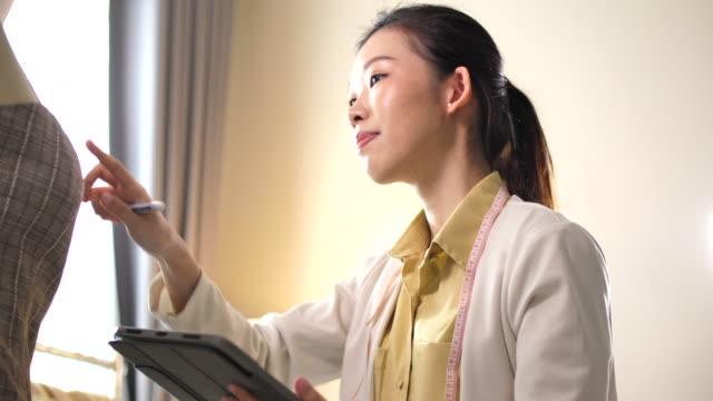 asian fashion designer, tailor and dressmaker adjusting clothes on tailoring mannequin - designer clothing stock videos & royalty-free footage