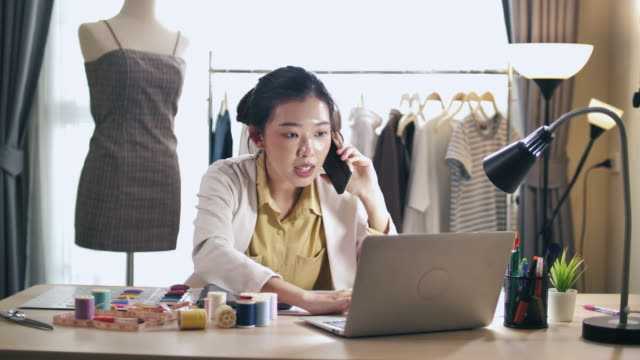 asian fashion designer talking on phone with her customer for designer solution - tailored clothing stock videos & royalty-free footage