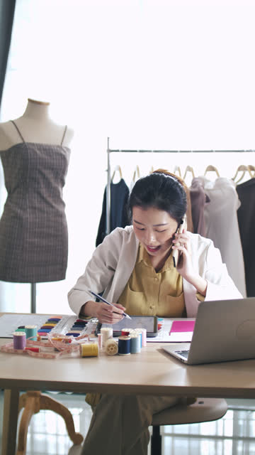 asian fashion designer talking on phone with her customer for designer solution, vertical - designer clothing stock videos & royalty-free footage