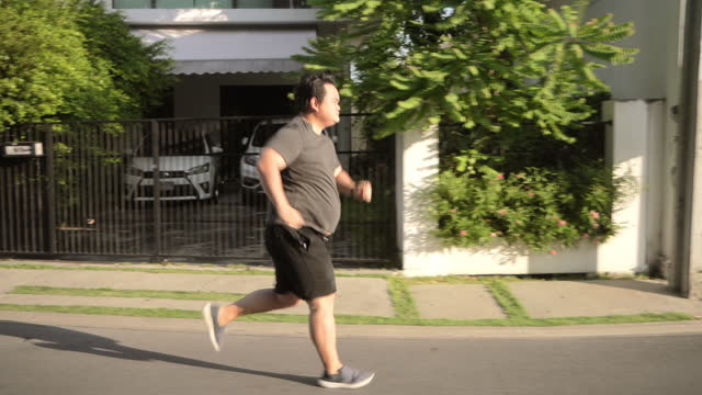 asian fat man running on road - large stock videos & royalty-free footage