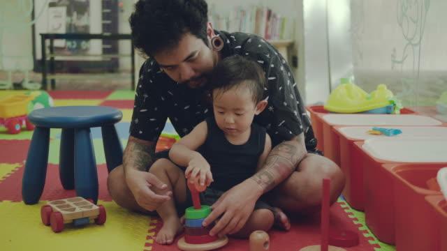 vídeos de stock, filmes e b-roll de asiático pai e criança brincando com brinquedos - bloco de construção
