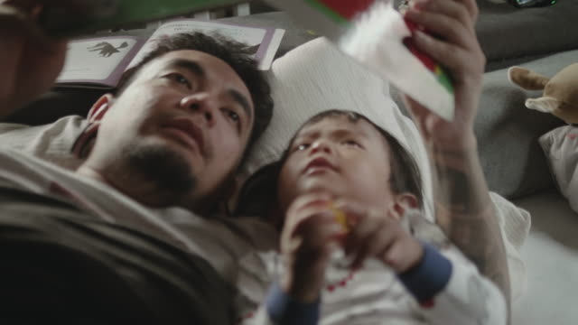 asian father and child, reading a book before bed time. - storytelling stock videos and b-roll footage