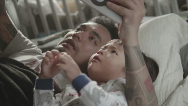 asian father and child, reading a book before bed time. - storytelling stock videos & royalty-free footage