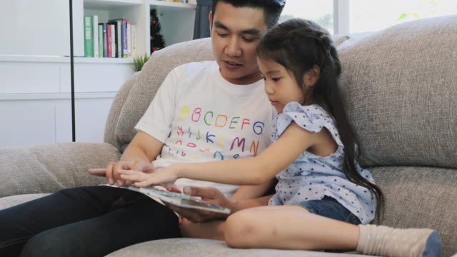 asian father and daughter select cd for listening music at home. - dvd player stock videos & royalty-free footage