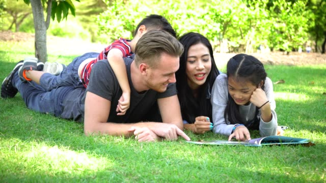asian father and mother reading story book in park - storytelling stock videos & royalty-free footage