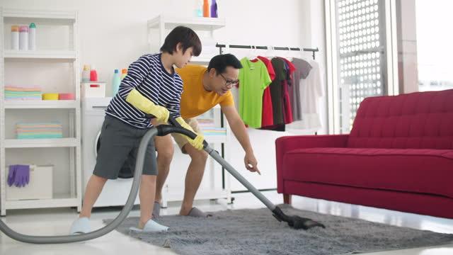 vídeos y material grabado en eventos de stock de padre e hijo asiáticos limpiando la habitación de la cama juntos - son