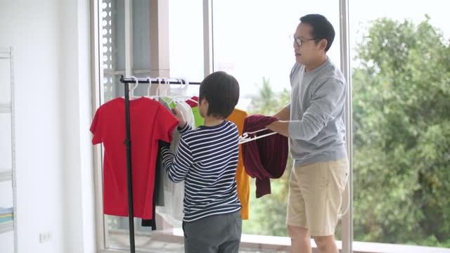 vídeos y material grabado en eventos de stock de padre asiático y su hijo que cuelgan ropa juntos - son