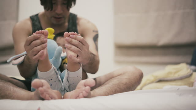 asian father and son having fun on the bed - genderblend stock videos & royalty-free footage
