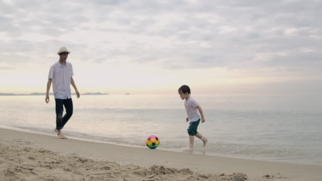 asian father and son playing ball on beach. - genderblend stock videos & royalty-free footage