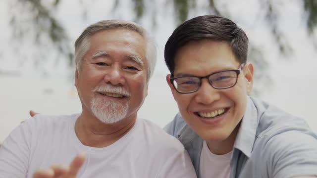 asiatische vater und sohn winken hände blick auf video-konferenz sagen hallo mit blick auf kamera lächelnd sehr glücklich - photo messaging stock-videos und b-roll-filmmaterial