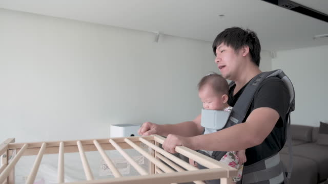 asian father assembling baby cot, with his daughter in baby carrier on his chest - genderblend stock videos & royalty-free footage