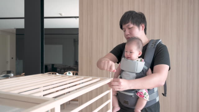 asian father assembling baby cot, with his daughter in baby carrier on his chest - crib stock videos & royalty-free footage