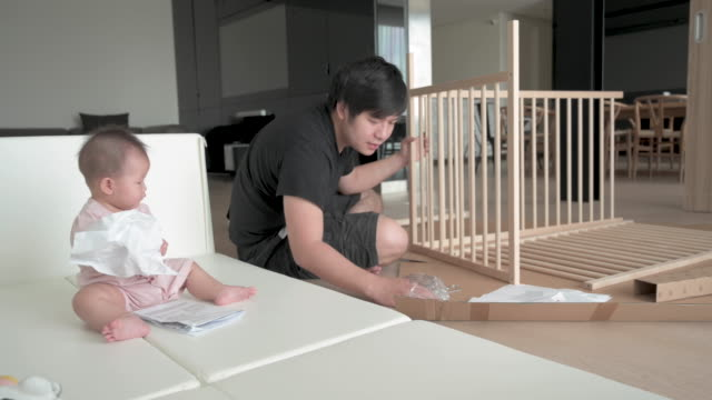 asian father assembling baby crib, baby playing in the play pen near by - genderblend stock videos & royalty-free footage
