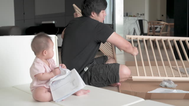 asian father assembling baby crib, baby playing in the play pen near by - crib stock videos & royalty-free footage