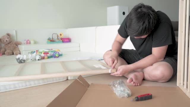 asian father assembling baby crib next to baby play pen - genderblend stock videos & royalty-free footage