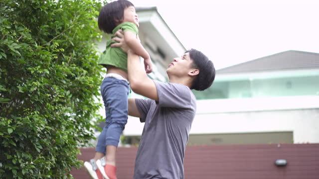 vídeos de stock, filmes e b-roll de pai asiático carregando seu filho para se exercitar no jardim da frente em casa - braço humano