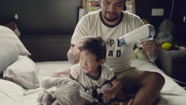 vídeos y material grabado en eventos de stock de asiático padre cambiarse de ropa a su bebé en la cama - cambiar pañal