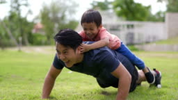 SLO MO Asian father doing push ups with little boy on his back, outdoors.