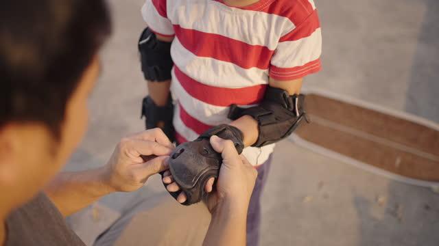 vídeos de stock, filmes e b-roll de pai asiático ajudando o filho a colocar luvas esportivas para o skate. - família jovem
