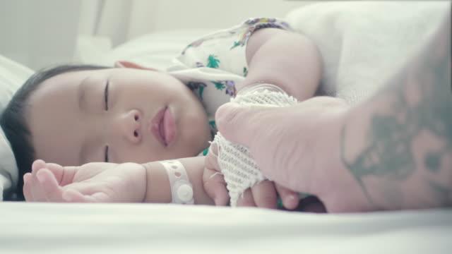 Aziatische vader zieke baby's hand slaap houden op bed.