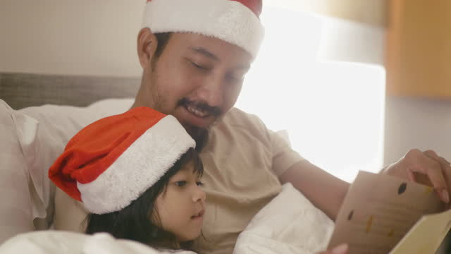 asian father is reading a christmas fairy tale with his daughter in the bedroom. - storytelling stock videos & royalty-free footage