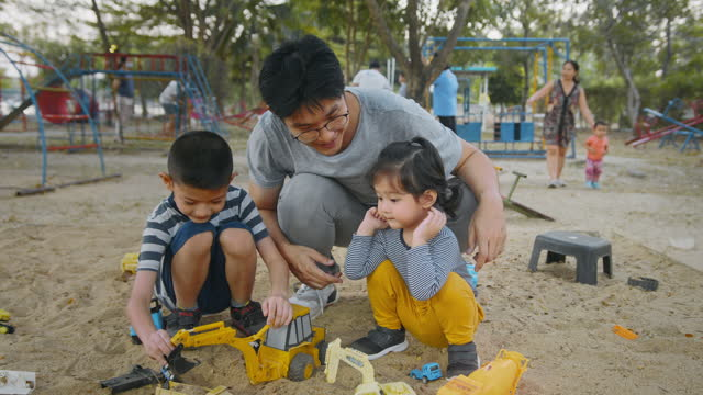 asian father playing with his son and daughter in the park. two sibling enjoy playing sand box with parent in weekend. family in the park concept - young family stock videos & royalty-free footage
