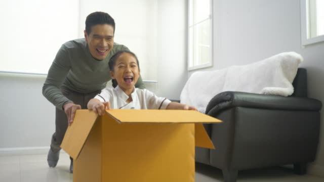 asian father pushin daugther in cardboard box feeling happy in house. - sliding stock videos & royalty-free footage