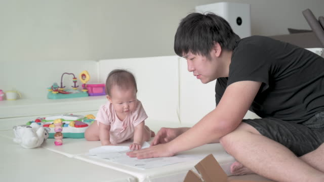 asian father reading manual for baby crib assembly, baby playing in the play pen near by - genderblend stock videos & royalty-free footage