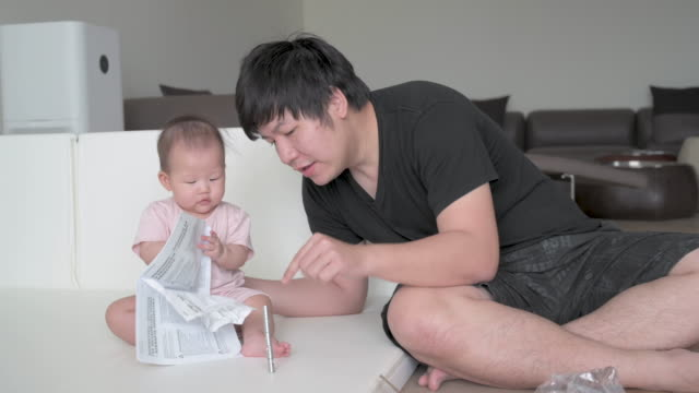 asian father trying to organise furniture parts, baby crumpling assembly manual - genderblend stock videos & royalty-free footage