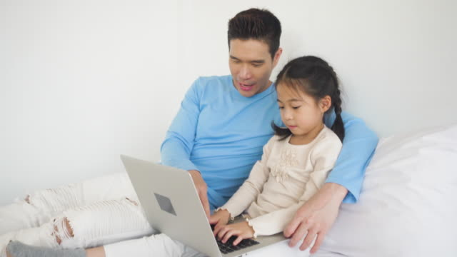 asian father using smartphone and tablet together with daughter sitting at home. - genderblend video stock e b–roll