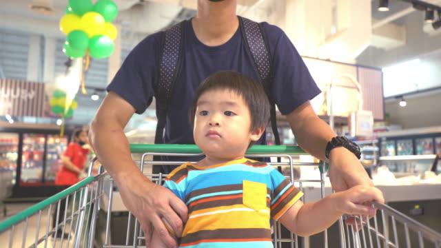 asiatischer vater trägt gesichtsmaske mit sohn einkaufen in einem supermarkt - einkaufswagen stock-videos und b-roll-filmmaterial