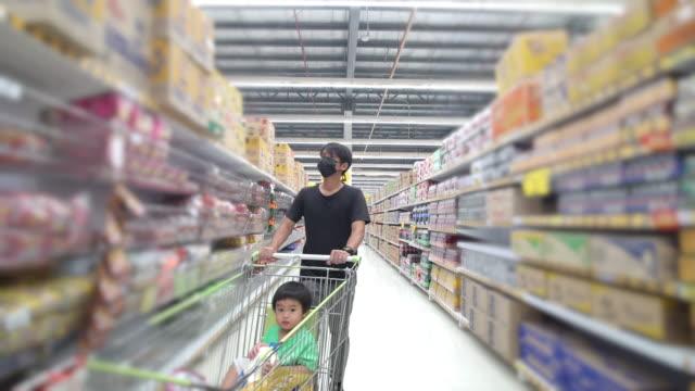 vidéos et rushes de père asiatique utilisant le masque de visage avec le magasinage de fils dans un supermarché - famille avec un enfant