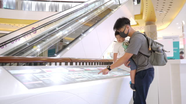 asian father wearing protective face mask holding baby boy looking at the map in the shopping mall - digital signage stock videos & royalty-free footage