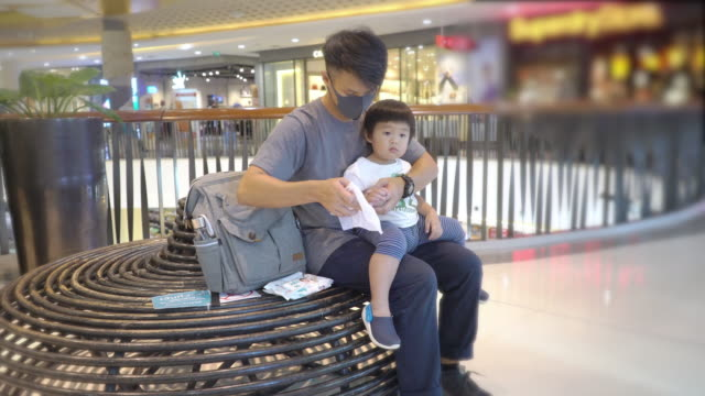 asian father wearing protective face mask using hand sanitizer gel with her son while sitting at the mall - wet wipe stock videos & royalty-free footage