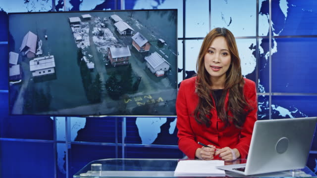 LD Asian female anchor presenting breaking news on floods