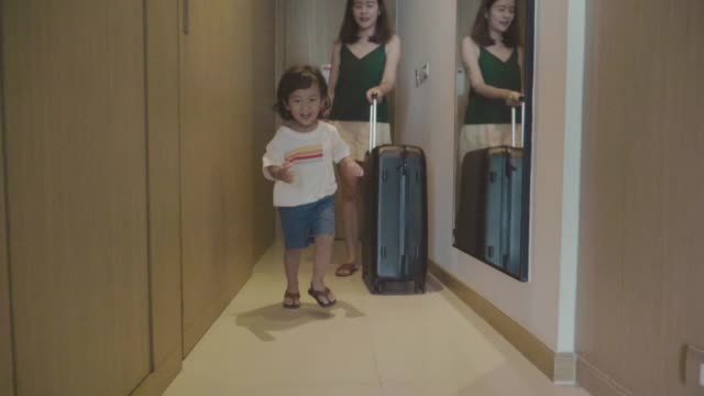 Asian Female And Little Boy Guest Walking Into Hotel Room With Her Suitcase.