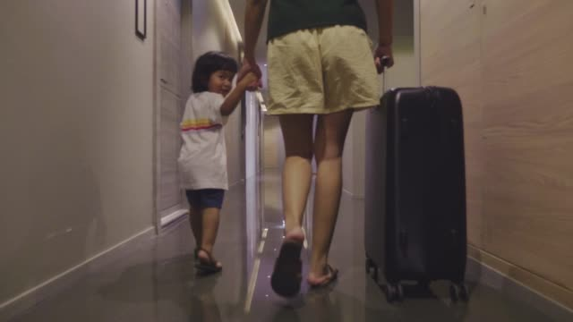 asian female and little boy guest walking into hotel room with her suitcase. - luggage stock videos & royalty-free footage