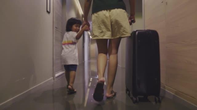 vídeos de stock, filmes e b-roll de convidado asiático da fêmea e do rapaz pequeno que anda no quarto de hotel com sua mala de viagem. - vista traseira