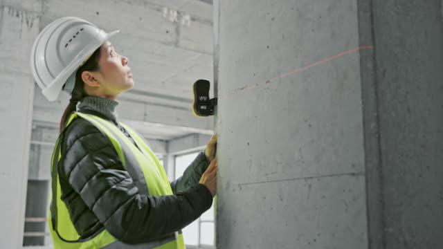 architetto donna asiatica che misura il fascio di supporto in un edificio industriale e lo marca - misurare video stock e b–roll