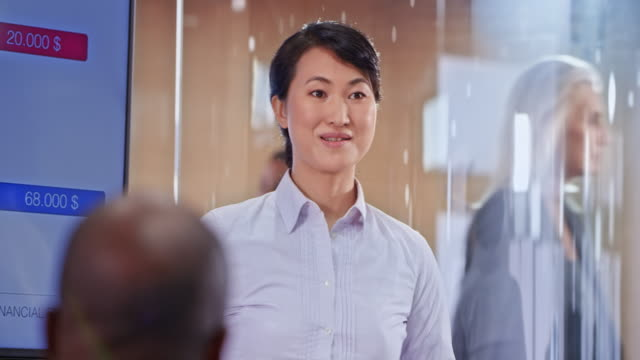 asian female business woman holding a presentation in a glass conference room - mature men stock videos & royalty-free footage