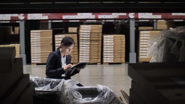 アジアの女性ビジネスウーマンワーカー工場ウェアハウスで彼女のデジタルタブレット上の在庫をチェックします。 - メガストア点の映像素材/bロール