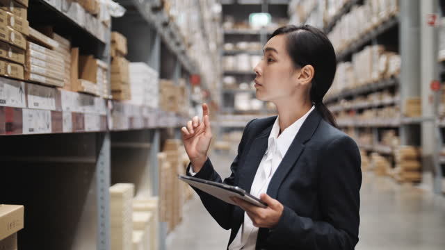 asian female businesswoman worker checking stock on her digital tablet in the factory warehouse - examining stock videos & royalty-free footage