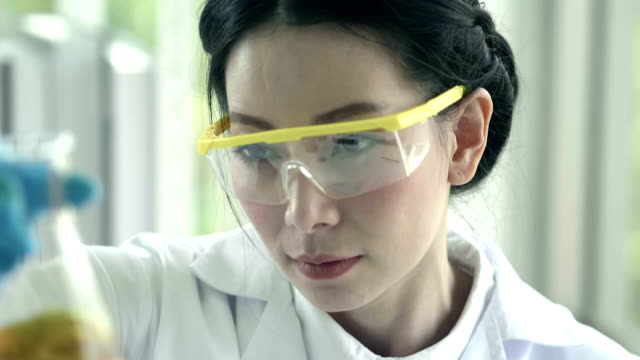 vídeos de stock e filmes b-roll de asian female chemist pouring yellow substance test tube - amostra médica