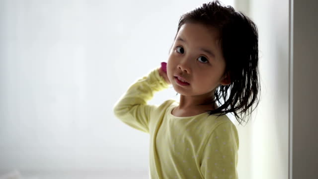 Asian female child combing her hair