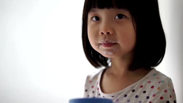 vidéos et rushes de enfant de femme asiatique, profitant de son tasse de lait - chinois