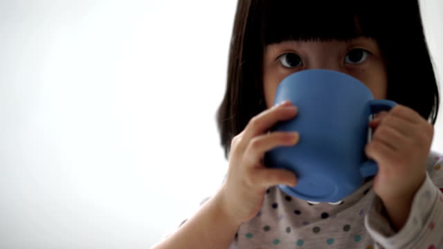 Asian female child enjoying her cup of milk