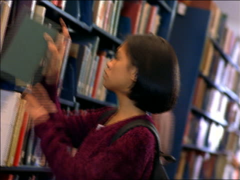 asian female college student pulling books from bookshelf in school library / boston, ma - 女子大生点の映像素材/bロール