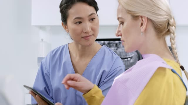 vídeos de stock, filmes e b-roll de dentista feminina asiática falando com seu paciente do sexo feminino e usando o tablet digital - dentista