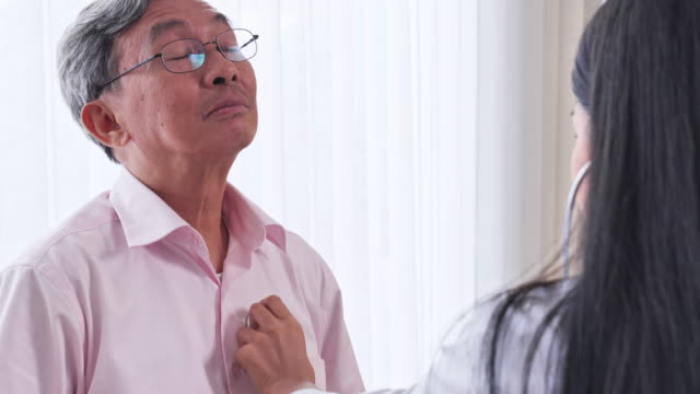 asian female doctor checking patient heart senior man in the examination room, senior asian man to get a health check by medical professionals. - medical examination room stock videos & royalty-free footage